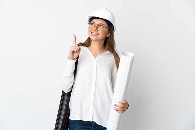 ヘルメットと白い壁に分離された青写真を保持している若いリトアニアの建築家の女性は素晴らしいアイデアを指しています