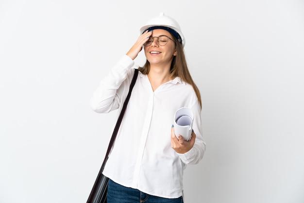 헬멧을 가진 젊은 리투아니아 건축가 여자와 많은 미소 흰 벽에 고립 된 청사진을 들고