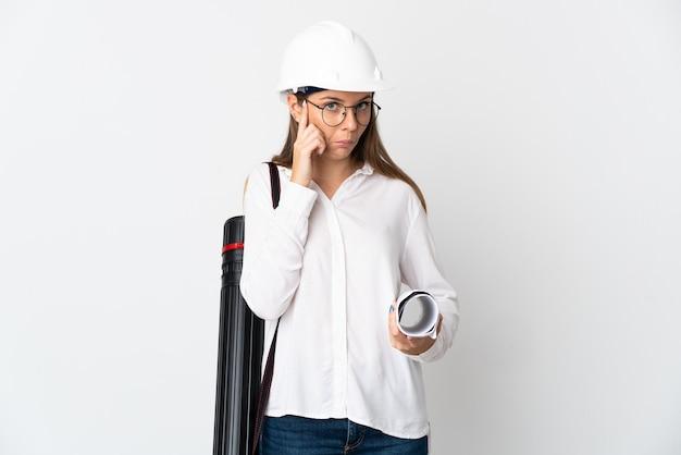 헬멧과 아이디어를 생각하는 흰 벽에 고립 된 청사진을 들고 젊은 리투아니아 건축가 여자