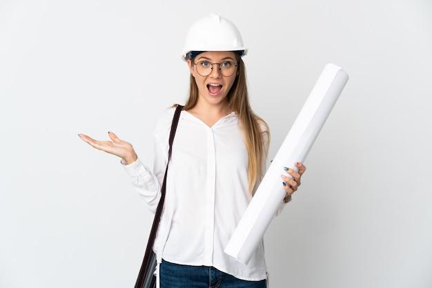Молодой литовский архитектор женщина в шлеме и держит чертежи, изолированные на белой стене с шокированным выражением лица