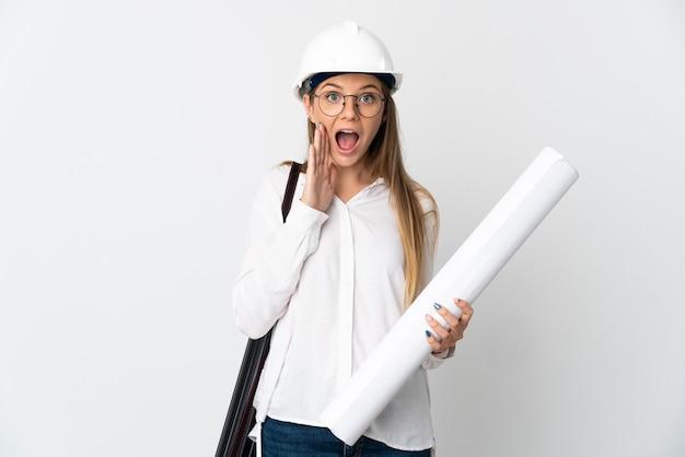 헬멧을 가진 젊은 리투아니아 건축가 여자와 놀라움과 충격 된 표정으로 흰 벽에 고립 된 청사진을 들고