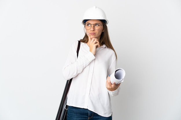 Young lithuanian architect woman with helmet and holding blueprints isolated on white background having doubts while looking up