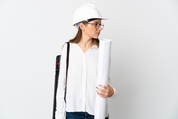 Young lithuanian architect woman with helmet and holding blueprints