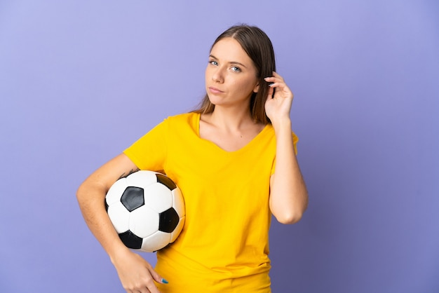 Женщина молодой литовский футболист изолирована на фиолетовом фоне с сомнениями