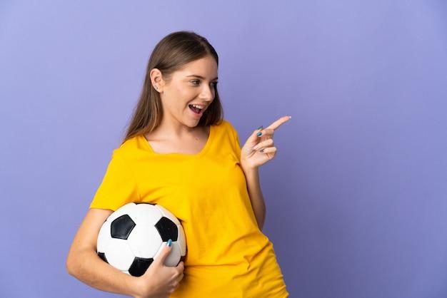 Молодой литовский футболист женщина изолирована на фиолетовом фоне, указывая пальцем в сторону и представляет продукт