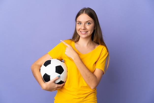 제품을 제시하기 위해 측면을 가리키는 보라색 배경에 고립 된 젊은 리투아니아 축구 선수 여자