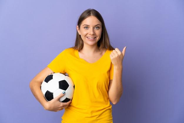 Молодой литовский футболист женщина изолирована на фиолетовом фоне, указывая в сторону, чтобы представить продукт