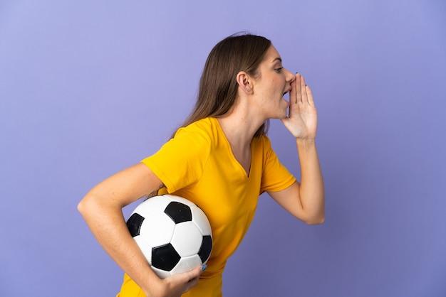 보라색 배경에 고립된 젊은 리투아니아 축구 선수 여성이 입을 크게 벌리고 소리를 질러