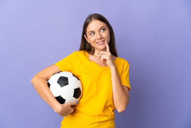 Молодой литовский футболист женщина изолирована на фиолетовом фоне, думая об идее, глядя вверх