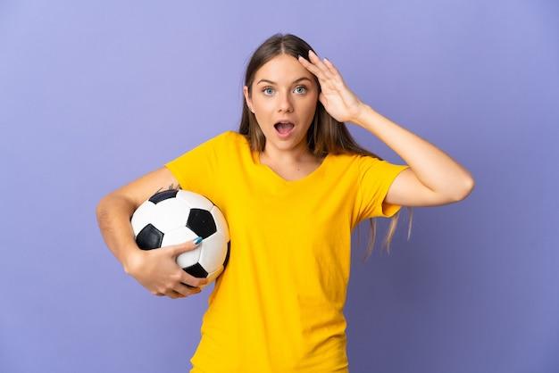 Женщина молодой литовский футболист, изолированные на фиолетовом фоне с выражением удивления