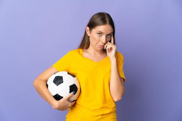 Молодой литовский футболист женщина изолирована на фиолетовой поверхности, думая об идее