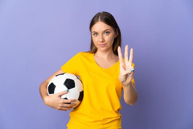 보라색 벽에 고립 된 젊은 리투아니아 축구 선수 여자 행복 하 고 손가락으로 세 세