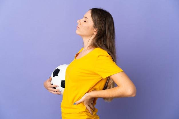 努力をしたために腰痛に苦しんで紫色の壁に孤立した若いリトアニアのサッカー選手の女性
