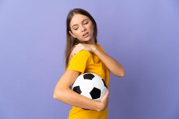 努力したために肩の痛みに苦しんで紫色の壁に孤立した若いリトアニアのサッカー選手の女性