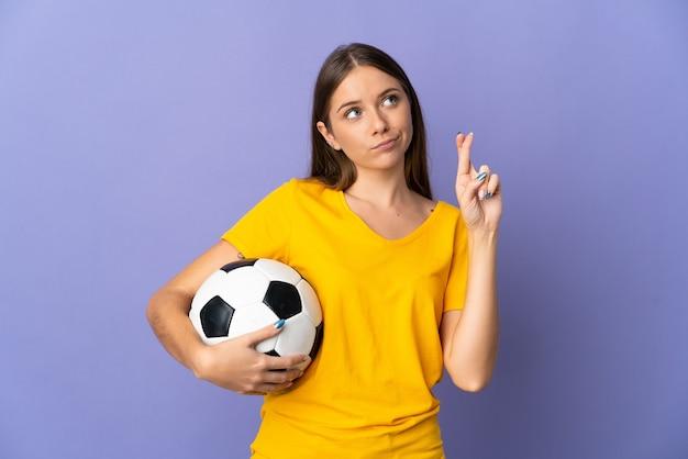 Молодая литовская футболистка изолирована на фиолетовой стене со скрещенными пальцами и желает всего наилучшего