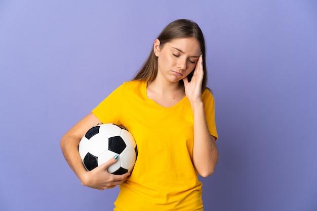 Молодой литовский футболист женщина изолирована на фиолетовой стене с головной болью