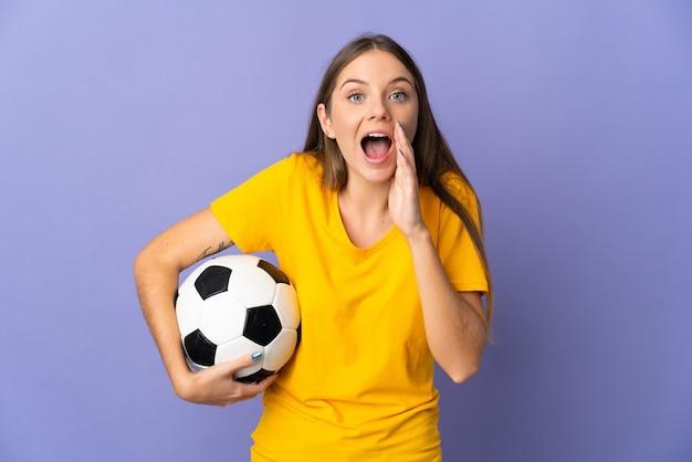 Молодая литовская футболистка изолирована на фиолетовой стене с удивленным и шокированным выражением лица