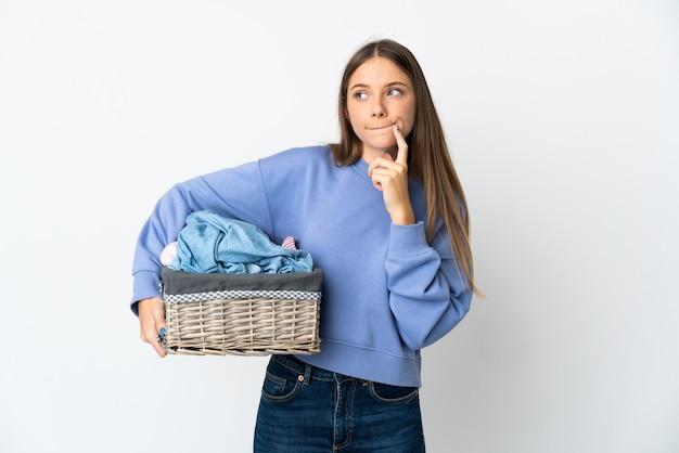 疑いと思考を持っている白い背景で隔離の服のバスケットを保持している若いリトアニアの女性
