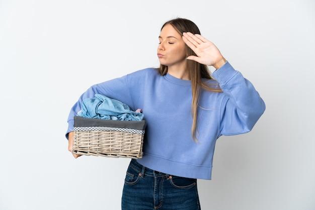 Молодая литовская женщина, держащая корзину с одеждой на белом фоне, делает жест стоп и разочарована