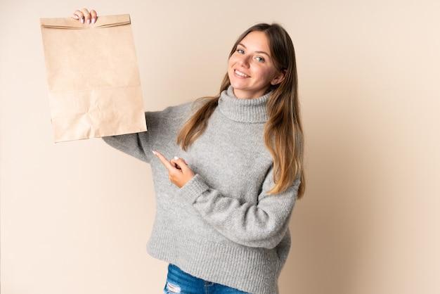 食料品の買い物袋を持ってそれを指している若いリトアニアの女性