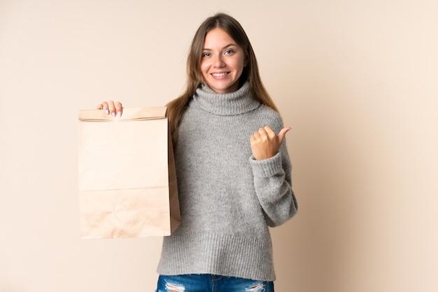 Молодая литовская женщина держит сумку для покупок и указывает в сторону, чтобы представить продукт