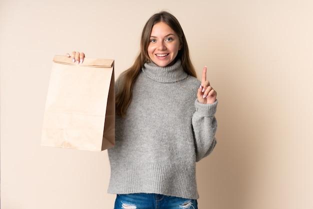 素晴らしいアイデアを指している食料品の買い物袋を持っている若いリトアニアの女性