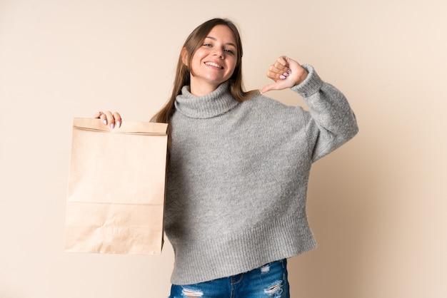 誇らしげで自己満足の食料品の買い物袋を持っている若いリトアニアの女性