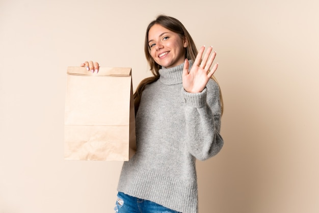 幸せな表情で手で敬礼する食料品の買い物袋を持っている若いリトアニアの女性