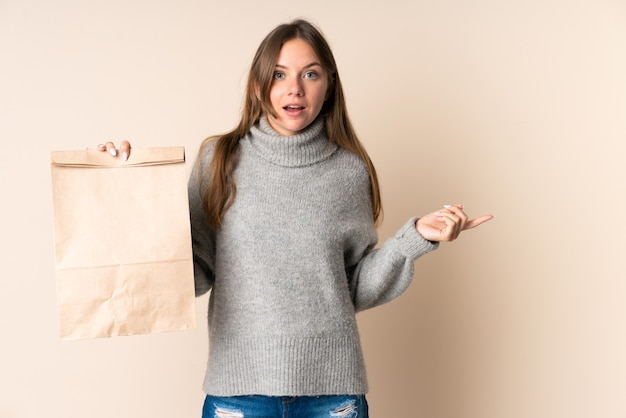 食料品の買い物袋を持って驚いて人差し指を横に向けている若いリトアニアの女性