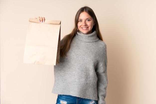 幸せな表情で食料品の買い物袋を保持している若いリトアニアの女性
