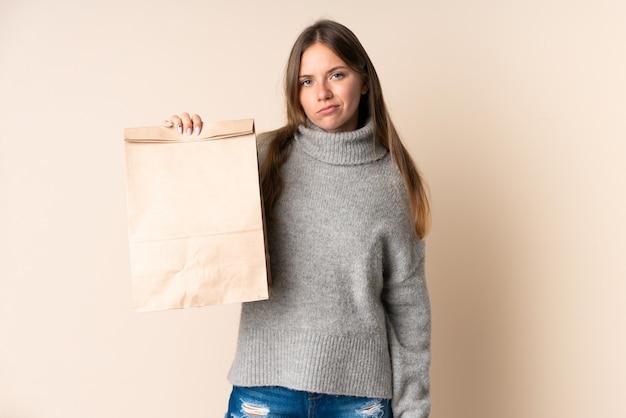悲しい表情で食料品の買い物袋を保持している若いリトアニアの女性