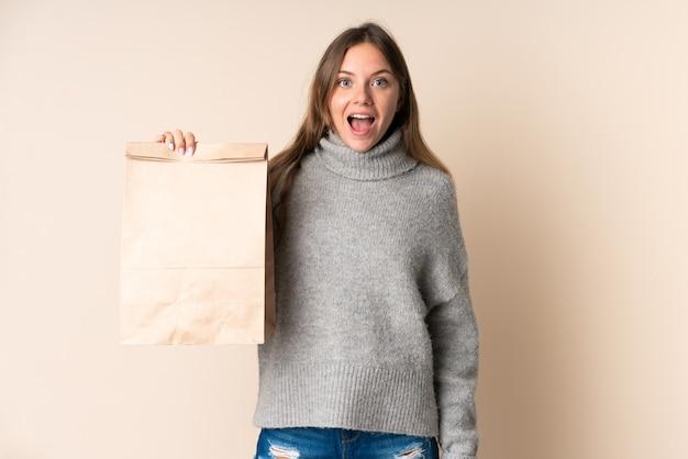 驚きとショックを受けた表情で食料品の買い物袋を持っている若いリトアニアの女性