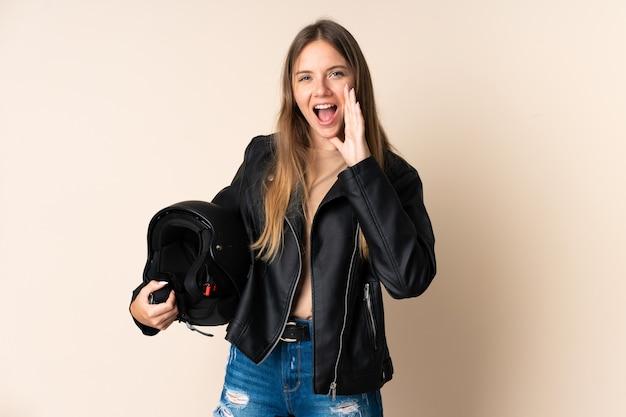 口を大きく開いてベージュの叫びで隔離のオートバイのヘルメットを保持している若いリトアニアの女性