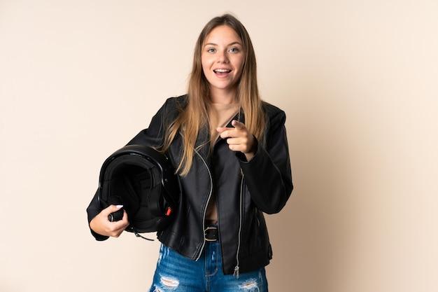 ベージュの壁に分離されたオートバイのヘルメットを保持している若いリトアニアの女性は驚いて正面を指しています