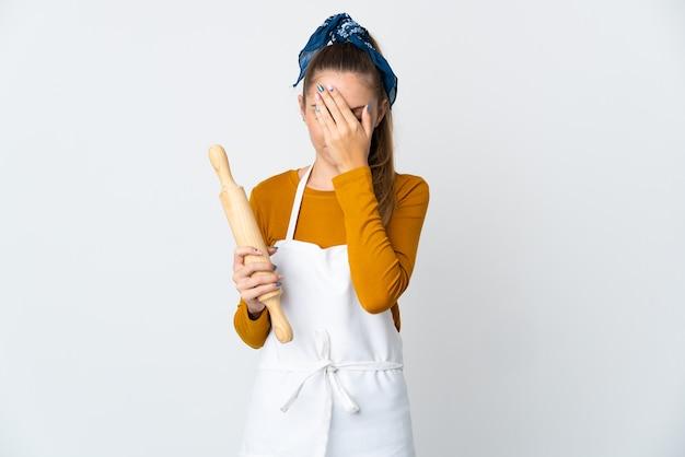 手で目を覆っている白い背景に分離された麺棒を保持している若いリトアニアの女性