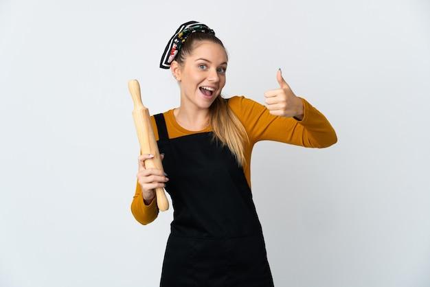 親指を立てるジェスチャーを与える白い背景に分離された麺棒を保持している若いリトアニアの女性