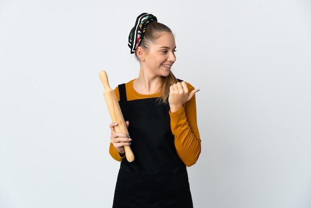 製品を提示する側を指している白い背景に分離された麺棒を保持している若いリトアニアの女性