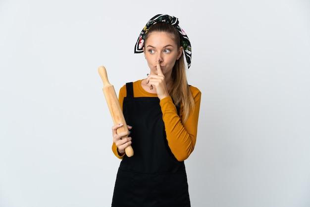 白い背景で隔離の麺棒を保持している若いリトアニアの女性は、口に指を入れて沈黙のジェスチャーの兆候を示しています