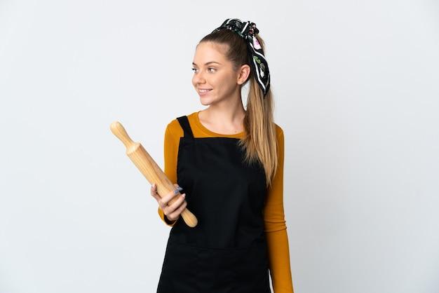 白い表面の側面に分離された麺棒を保持している若いリトアニアの女性
