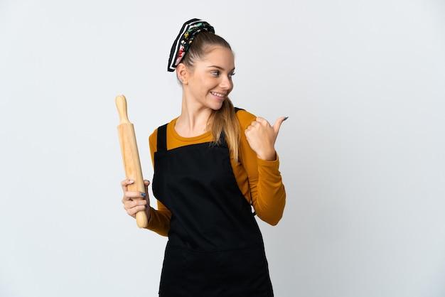 製品を提示する側を指している白い表面に分離された麺棒を保持している若いリトアニアの女性