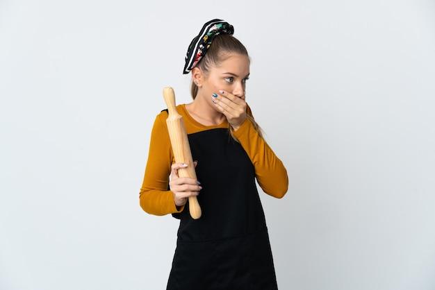 口を覆って横を向いている白い壁に分離された麺棒を保持している若いリトアニアの女性