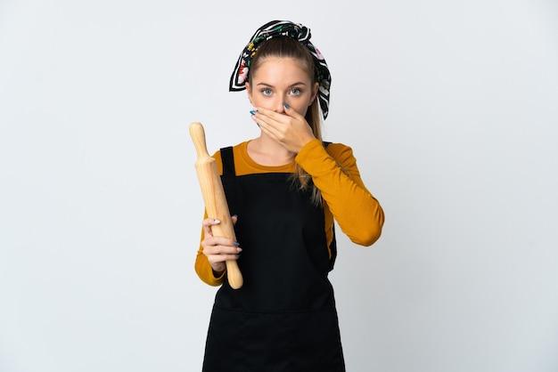 手で口を覆う白い壁に分離された麺棒を保持している若いリトアニアの女性