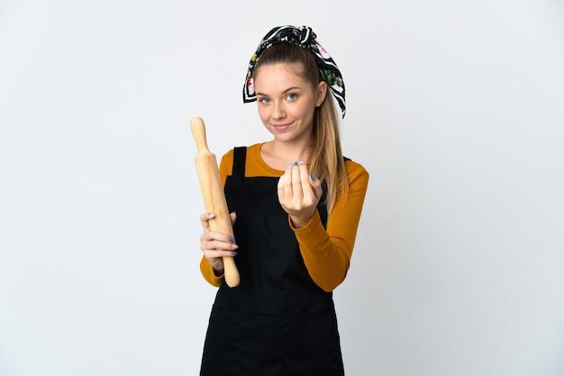 手で来るように誘う白い壁に隔離された麺棒を保持している若いリトアニアの女性。あなたが来て幸せ
