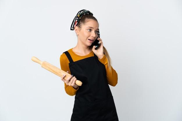 누군가와 휴대 전화로 대화를 유지하는 흰 벽에 고립 된 롤링 핀을 들고 젊은 리투아니아 여자