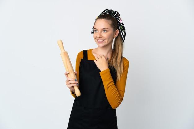 웃는 동안 올려 흰 벽에 고립 된 롤링 핀을 들고 젊은 리투아니아 여자