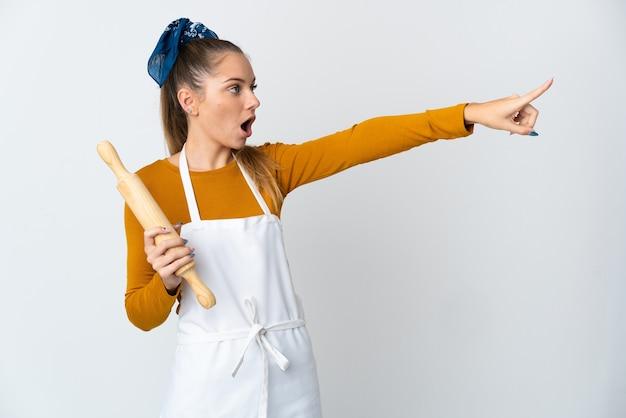 離れて指している白い壁に分離された麺棒を保持している若いリトアニアの女性