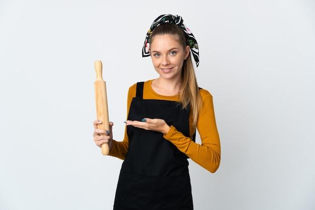 に向かって笑顔を見ながらアイデアを提示する白い壁に分離された麺棒を保持している若いリトアニアの女性