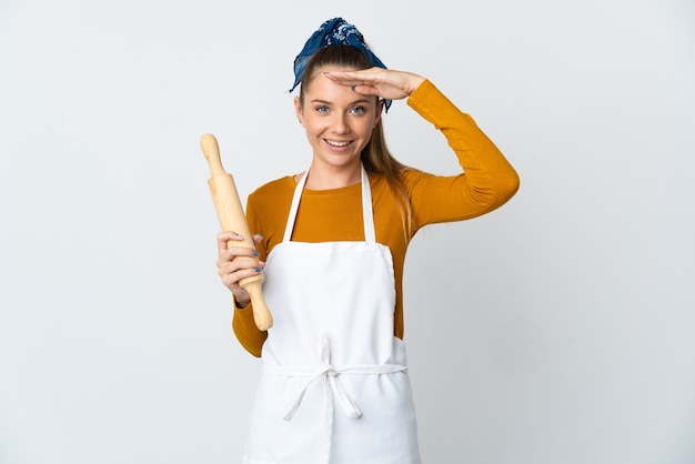 幸せな表情で手で敬礼する白い壁に分離された麺棒を保持している若いリトアニアの女性