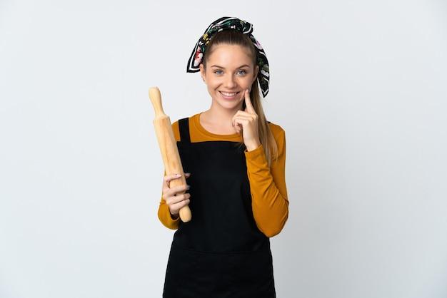 행복하고 즐거운 표정으로 웃고 흰 벽에 고립 된 롤링 핀을 들고 젊은 리투아니아 여자
