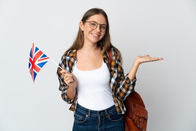 広告を挿入するために手のひらに架空のコピースペースを保持している白い背景で隔離のイギリスの旗を保持している若いリトアニアの女性